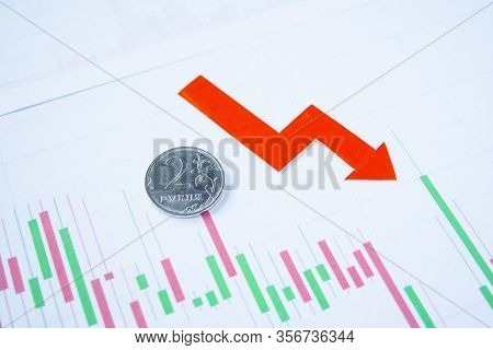 Two Rouble Coin On Currency Graph With Red Arrow Down. Exchange Rate Chart. Ruble Depreciation. Exch