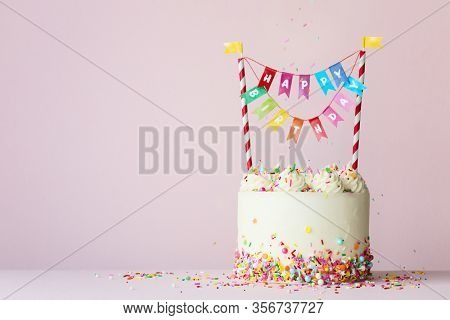 Birthday cake with brightly colored happy birthday banner