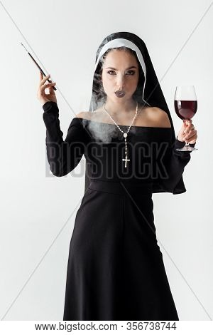 Passionate Nun With Glass Of Wine Smoking A Cigarette In Mouthpiece Isolated On Grey