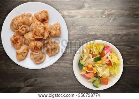 Dumplings On A White Plate On Black Wooden Background. Dumplings In Tomato Sauce With Salad. Dumplin