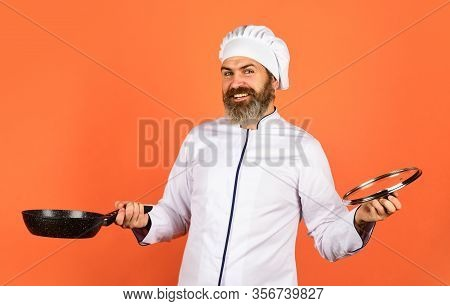 Happy Cook Man Hold Frying Pan. Chef In Uniform Cooking Soup. Restaurant Kitchen. Cooking Lunch In K