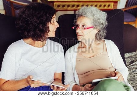 Daughter Explaining Internet App Specifics To Senior Mother. Middle Aged Woman And Elderly Lady, Hol
