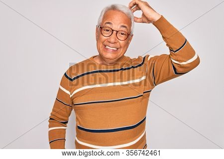 Middle age senior grey-haired handsome man wearing glasses and casual striped sweater confuse and wonder about question. Uncertain with doubt, thinking with hand on head. Pensive concept.