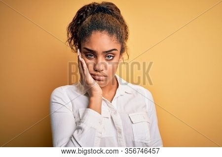 Young beautiful african american girl wearing casual shirt standing over yellow background thinking looking tired and bored with depression problems with crossed arms.