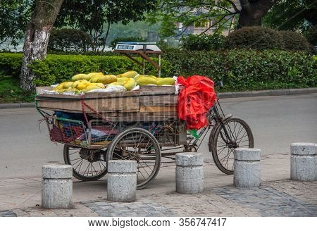 Guilin, China - May 10, 2010: Downtown. Old Tricycle Pedal Bike With Wooden Load Compartment Full Of