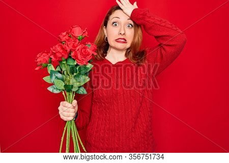 Young beautiful redhead woman holding bouquet of red roses flowers over isolated background stressed with hand on head, shocked with shame and surprise face, angry and frustrated. Fear and upset