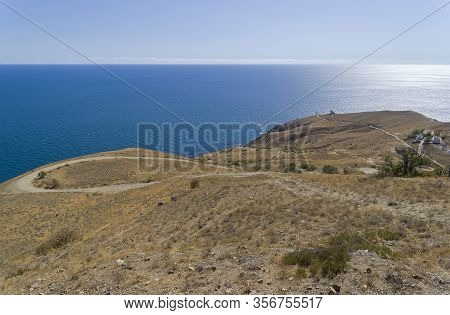 Panorama Of A Mountainside On The Seashore With A Winding Dirt Road Going Down To The Lighthouse. Ca