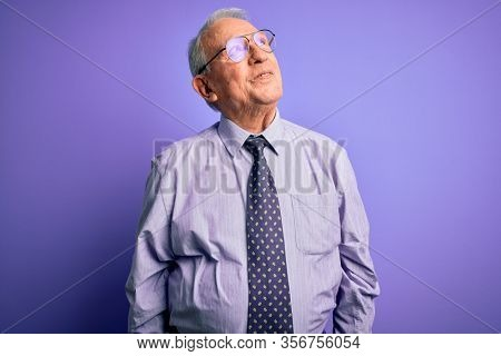 Grey haired senior business man wearing glasses standing over purple isolated background smiling looking to the side and staring away thinking.
