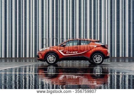 Brest, Belarus - Feb 23, 2020: Toyota C-hr 2019 Car On Street City Against Striped Wall