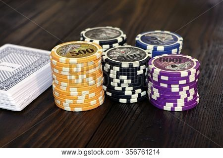 Playing Cards And Poker Chips On A Wooden Table. Stack Of Chips For Poker.