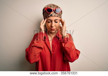 Middle age brunette woman wearing handkerchief on head and shirt over white background with hand on head for pain in head because stress. Suffering migraine.