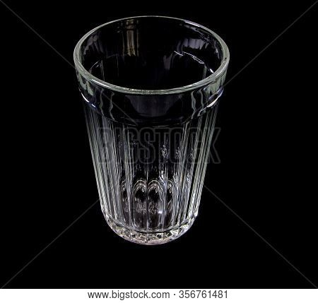 Empty Faceted Glass On A Black Background. Close-up.