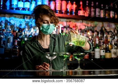 Young Woman Bartender In Medical Mask Professionally Pours Drink From Large Glass Into Wineglasses.