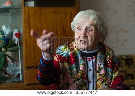 An old woman in bright clothes and a scarf gestures sitting at the table. Elderly pensioner.