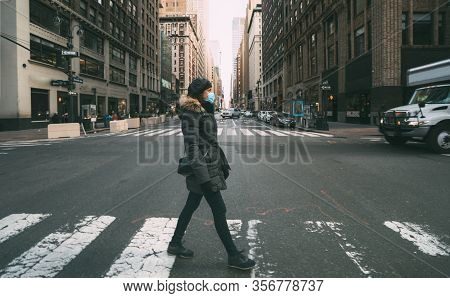 Woman Wearing Surgical Mask Going Through Crosswalk In New York, Midtown Manhattan