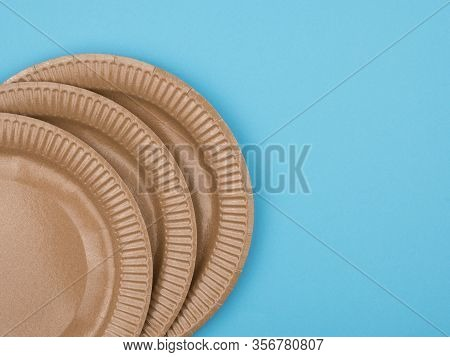 Cardboard Plates On A Blue Background. The View From The Top. Disposable Ware.