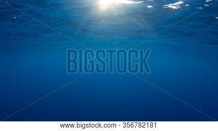 Underwater background with sunburst on surface of clear blue ocean
