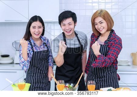 Group Friends Wear Apron Holding Join Fist Together While Standing In The Kitchen, They're Brotherho