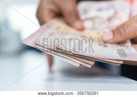 Weak Baht, Thai Baht Banknotes, Businessman's Hands Counting Money. One Thousand Baht. (thb) Is Offi