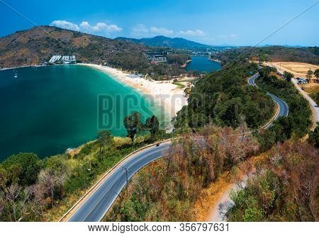 Aerial view of the tropical beach of Nai Harn and asphalt road along the coastline on Phuket island in Thailand
