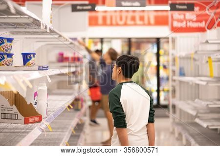 An Asian Young Man Is Looking For Powdered Detergent On Empty Shelves In Coles Supermaket, Covid 19