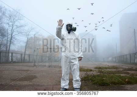 Environmentalist Doing Stop Gesture While Standing On Foggy Street With Flying Birds On Background.
