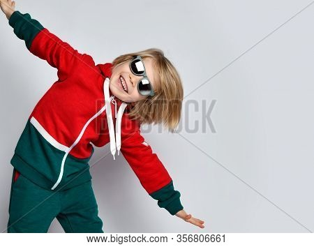Portrait Of Happy Active Frolic Blond Kid Boy In Dark Gray And Red Hoodie, Pants And Sunglasses Is P