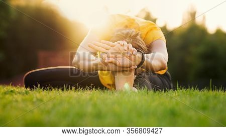 Young Attractive Woman Practicing Yoga In The Park At Sunset. Outdoor Sport Activity. Practice Yoga