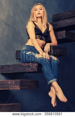 Beautiful Sensual Adult Woman In A Bra And Jeans Posing On A Wooden Cantilever Stairs. Looking At Ca