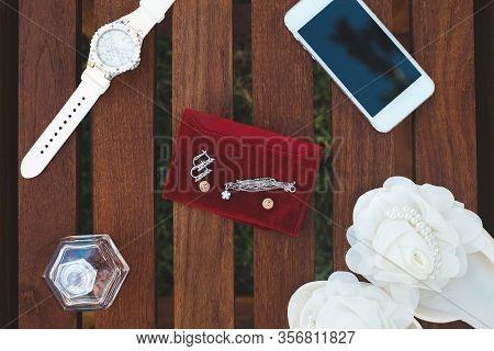Wedding Paraphernalia Of The Bride. Sandals. Phone. Earrings. Spirits.