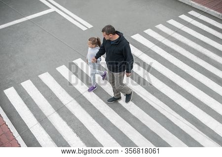 Man And Child On A Zebra Crossing Trespassing By Crossing The Street. In The Summer On The Street Ki