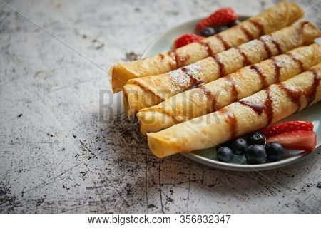 Plate of delicious crepes roll with fresh fruits and chocolate placed on rusty table. Top view, flat lay.