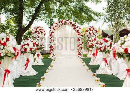 Wedding Ceremony Outdoors. Wedding Arch Decorated With Red Flowers.