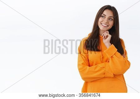 Intrigued And Thoughtful Caucasian Girl In Orange Hoodie, Touch Chin Tilt Head And Looking Left Curi