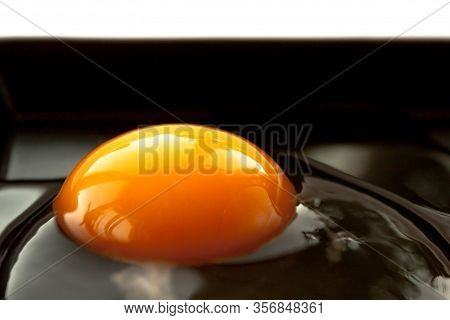 Broken Cracked Raw Fresh Crushed Yellow Color Egg White And Yolk On Black Plate On White Background