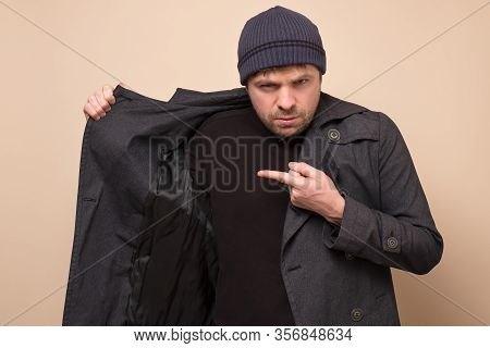 Young Caucasian Speculator Man Pointing On His Coat On Empty Place Hiding Deficit Food.