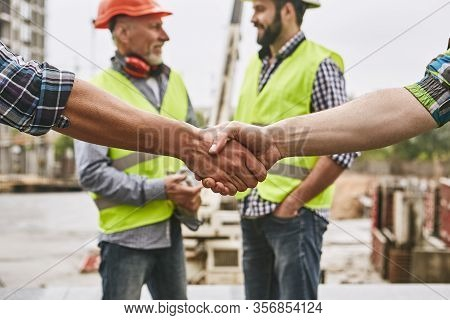We Did It Close Up Photo Of Builders Shaking Hands Against Cheerful Colleagues While Working Togethe