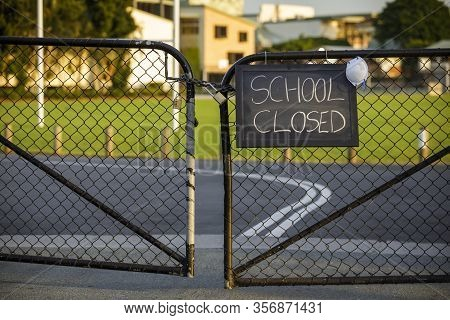 School Closed Sign With Protective Mask Hanging On A Padlocked Gate, School Closed Or Shutdown Conce