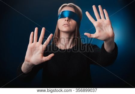Girl Blindfolded, With A Blue Ribbon, Looking For Something With Her Hands, Playing On A Blue Backgr