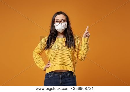 Chine girl with glasses and medical mask pointing hand up in studio