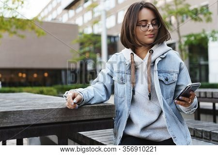 Portrait Of Young Modern Hipster Girl In Denim Jacket, Glasses Sitting Outdoors At City Square, Park