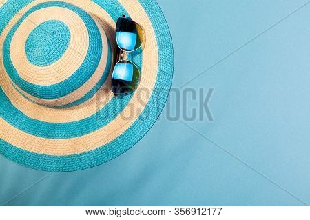 Top View On Beach Accessories On Turquoise Blue Background - Sunglasses And Striped Blue Hat In The