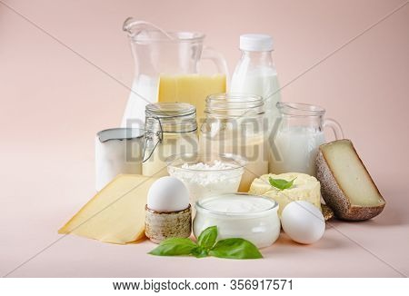 Fresh Dairy Products, Milk, Cottage Cheese, Eggs, Yogurt, Sour Cream And Butter On Pink Background