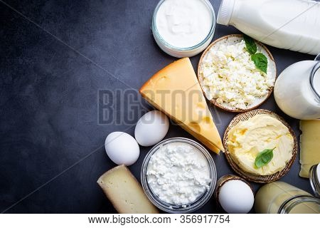 Fresh Dairy Products, Milk, Cottage Cheese, Eggs, Yogurt, Sour Cream And Butter On Black Background,