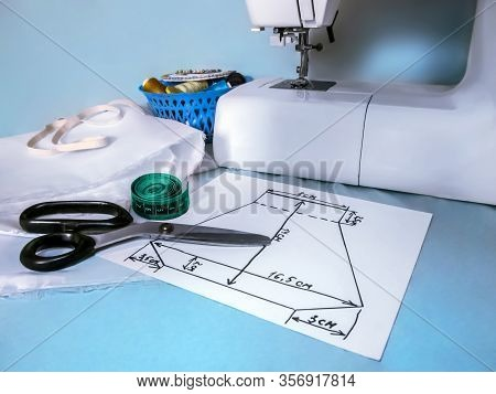 Handmade Sewing Pattern Of A Face Mask Lies Near The Sewing Machine And Sewing Accessories. The Conc