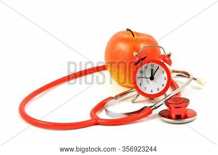 A Red Apple With An Alarm Clock And Stethoscope Over A White Background To Represent Medical Themes.