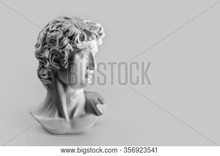 Gypsum Statue Of Davids Head. Michelangelos David Statue Plaster Copy On Grey Background With Copysp
