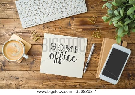 Home Office And Working From Home Concept. Table Workplace With Keyboard Computer, Notepad And Coffe