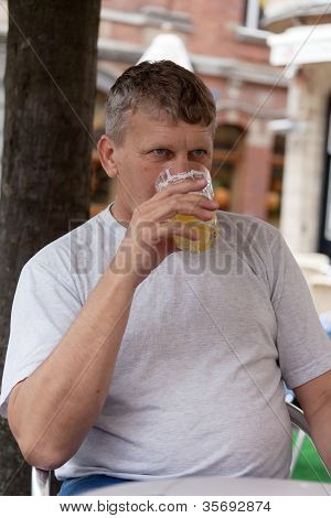 mature man drinks beer in street cafe