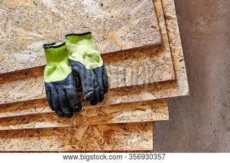 Osb Slab Building Material Made From Reborn Sawdust. They Lie In A Pile, Yellow Protective Gloves Li